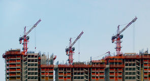 Parallel Lines. Three Cranes perfectly parallel atop incomplete apartment buildings under construction stock photography