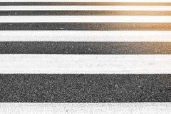 Parallel lines of crosswalk, asphalt rough pattern, no people, sunlight in one corner royalty free stock photo