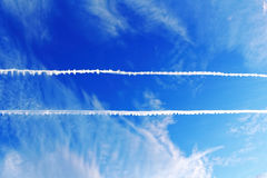 Parallel plane trails in sky. The vapor of two parallel running plane trails in the blue sky. Air traffic Royalty Free Stock Image