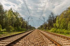 Parallel railway tracks and overhead lines. Are heading towards the cloudy sky on the horizon and through the forest royalty free stock image