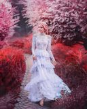 Parallel reality, fabulous mermaid in underwater world walks path, girl in red surrealistic world with coral trees stock photos