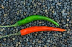 Parallel red green hot peppers long pods base seasoning for meat giving a drink to the background of black peppercorns culinary ba. Se royalty free stock image