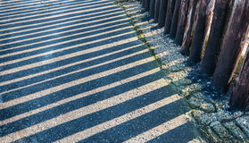 Parallel shadows of a row of wooden poles Stock Image
