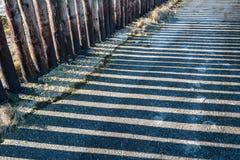Parallele Schatten einer Reihe der hölzernen Pfosten Stockbild