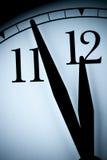 Parallell väggklocka i ett lågt ljus med svarta händer och nummer med få minuter som lämnas till 1/2 - timmetimme Fotografering för Bildbyråer