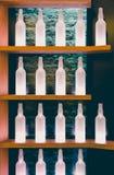 Parallella trähyllor med rad av vita alkoholflaskor Arkivfoto
