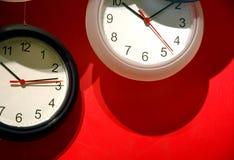 Parallellla klockor på den röda väggen Arkivfoton