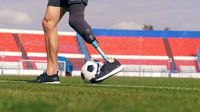 Paralympian with a bionic leg is training with a football. 4K stock footage