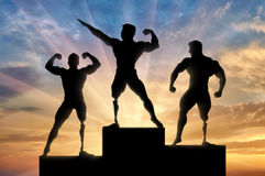 Paralympic bodybuilders be awarded sunset background. Paralympic bodybuilders stand on pedestal and rewarding on sunset background. Concept handicapped and sport Stock Image