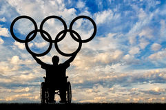 Paralympic disabled person in wheelchair hold olympic rings. Concept sports and willpower Stock Photos