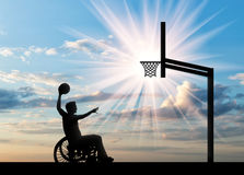 Paralympic disabled person in wheelchair playing basketball in afternoon. Paralympic disabled person in wheelchair rolls ball into basket day. Concept sport and Stock Photo