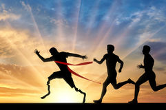 Paralympic runner with prosthesis and normal runners. Paralympic handicapped runner with prosthesis and normal runners compete sunset. Concept sport and Stock Image