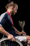 Paralympic in wheelchair with gold medals on neck looking at champion goblet Stock Photos
