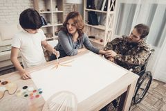 Paralyzed Soldiers`s Son Is Drawing A Picture. Kid With Tassel. Resting Together. Child And Wife. Camouflage Uniform. Feelings Showing. Home Leisure. Disabled stock photography