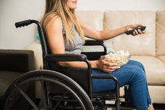Paralyzed woman watching TV on wheelchair Royalty Free Stock Photos