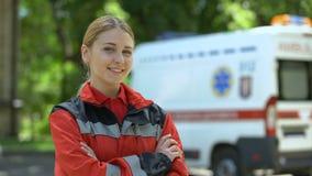 Paramédico de sexo femenino amistoso que presenta para la cámara, ambulancia en el fondo, vidas de ahorro metrajes