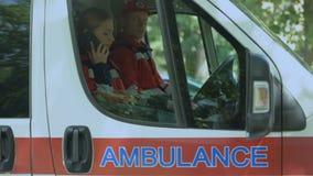 Paramédico de sexo femenino que usa smartphone para llamar al paciente, equipo de la ambulancia de servicio metrajes