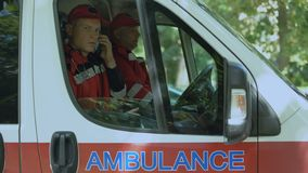 Paramédico de sexo masculino que contesta en la llamada de paciente, equipo profesional de la ambulancia, 911 almacen de video
