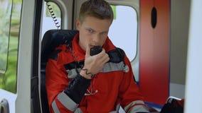 Paramédico de sexo masculino que habla por la radio, puerta de cierre de la ambulancia para expulsar en llamada metrajes