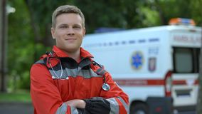 Paramédico de sexo masculino que presenta para la cámara, ambulancia en el fondo, profesionalismo almacen de metraje de vídeo