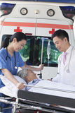Paramédico fêmea e doutor que rodam em um paciente idoso em uma maca na frente de uma ambulância Foto de Stock Royalty Free