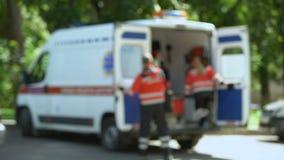 Paramédico que cabecea a la cabeza, caminando a la ambulancia con el paciente, primeros auxilios calificados metrajes