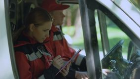 Paramédico que escribe informe en la ambulancia, sonriendo a la cámara, profesionales de servicio almacen de video