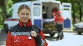 Paramédico que presenta para la cámara, equipo de la ambulancia que transporta al paciente a la clínica almacen de video