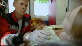 Paramédico que toca el hombro del paciente que murió en la ambulancia, compasión, dolor metrajes