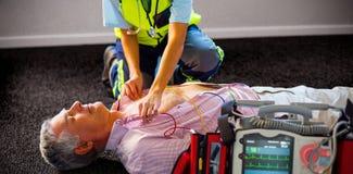 Paramédico que usa um desfibrilador externo em um paciente inconsciente imagens de stock royalty free