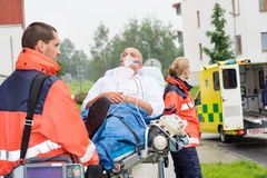 Paramédicos con el paciente en ayuda de la ambulancia del ensanchador Fotografía de archivo