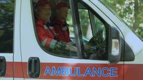 Paramédicos de sexo masculino que miran la cámara, equipo de la ambulancia listo para expulsar en llamada almacen de metraje de vídeo
