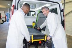 Paramédicos que cargan el ensanchador en la ambulancia imagen de archivo libre de regalías