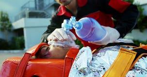 Paramédicos que examinam a menina ferida