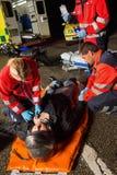 Paramédicos que examinam o motorista ferido do homem da motocicleta foto de stock