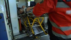 Paramédicos que llevan al paciente en ensanchador en la ambulancia, ayuda calificada rápida metrajes