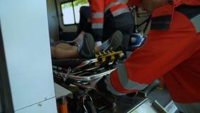 Paramédicos que llevan a la mujer en ensanchador en la ambulancia, equipo de rescate calificado almacen de metraje de vídeo