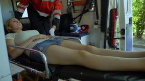 Paramédicos que sacan a la mujer en ensanchador de la ambulancia, transporte a la clínica metrajes
