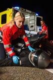 Paramédico que ayuda al conductor de la moto en la noche Imagenes de archivo