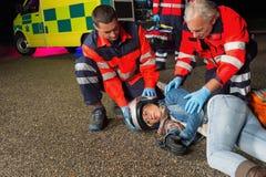 Paramédicos que ayudan al conductor de la moto que miente en el camino Fotos de archivo libres de regalías