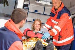 Paramédicos que ayudan a la mujer en brazo roto ambulancia Imágenes de archivo libres de regalías