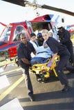 Paramédicos que descargan al paciente del helicóptero Fotografía de archivo libre de regalías