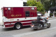 Paramedic 1. A fire rescue vehicle blazes by with a police escort stock photography