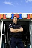Paramedic and ambulance. Paramedic on ambulace looking out for trouble with blue sky Royalty Free Stock Photos