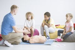 Paramedic and children during training. Paramedic teaching multicultural group of children how to resuscitate during training with manikin royalty free stock photo