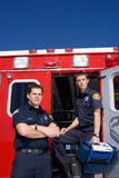 Paramedic and colleague by open door of ambulance, portrait, low angle view Royalty Free Stock Photos