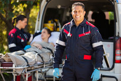 Paramedic colleague patient. Handsome paramedic with colleague and patient on background Stock Images