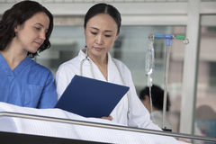 Paramedic and doctor looking down at the medical record of patient on a stretcher in front of the hospital Stock Photos