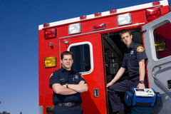 Paramedic by door of ambulance by colleague, portrait, low angle view Royalty Free Stock Photography