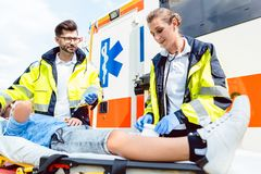 Paramedic and emergency doctor caring for injured boy. On stretcher stock image